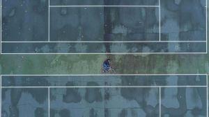 アイキャッチ画像 上空撮影によるテニスコートに横たわり、自転車に乗っているように見せているだまし絵 デザイン発注の教科書 